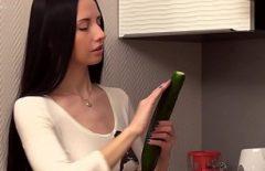 امرأة سمراء فتاة تعطي زيوت التشحيم على الخيار لتنزلق جيدا في بوسها
